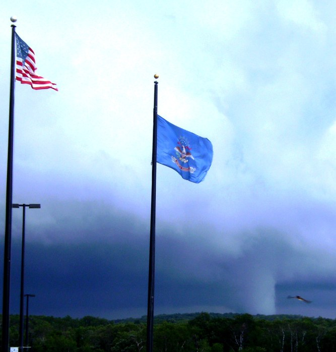 Belcourt, ND: An American bald eagle flies towards the flags as a tornado rips through our area...a sure sign that we wer truly being watched over!