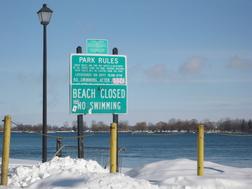Marine City, MI: Beach is closed No swimming! sign with a light pole next to it. The sun shining on top of the water. Snow covers most of the sand.Yellow poles that hold chains.